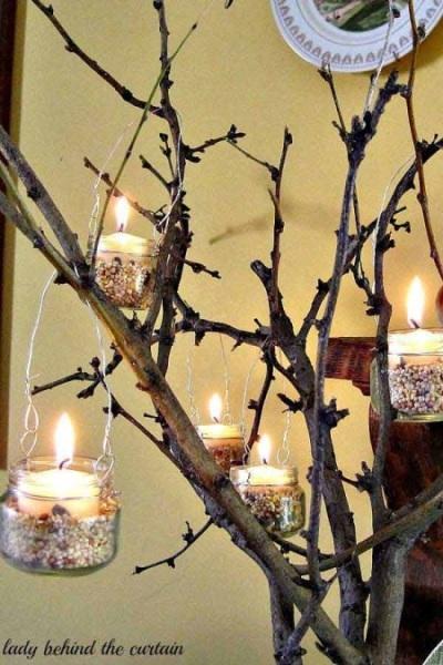 Gantungkan beberapa tempat lilin hias pada batang pohon sebagai hiasan